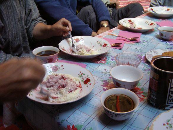 Lecker Milchreis mit Kirschen zum Frühstück, serviert auf einem niedrigen Tisch in einer Jurte