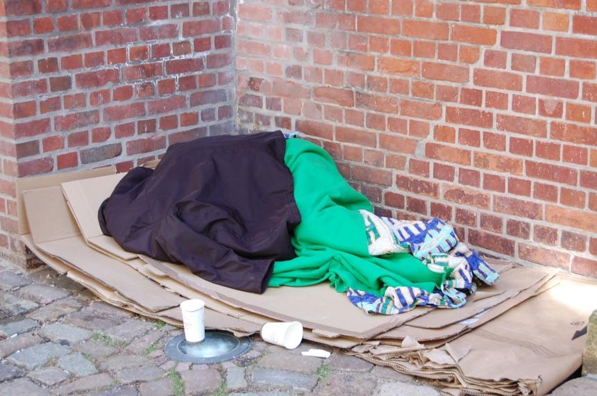 Obdachloser an einer Kirchenmauer