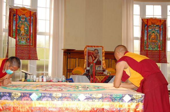 Im Hintergrund der Altar mit dem Foto des Dalai Lamas
